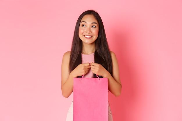 Concetto di bellezza, moda e stile di vita. ritratto di ragazza asiatica sognante e divertita esplora centri commerciali con sconti speciali e offerte di vendita di fine estate, tenendo la borsa della spesa e guardati intorno con un sorriso.