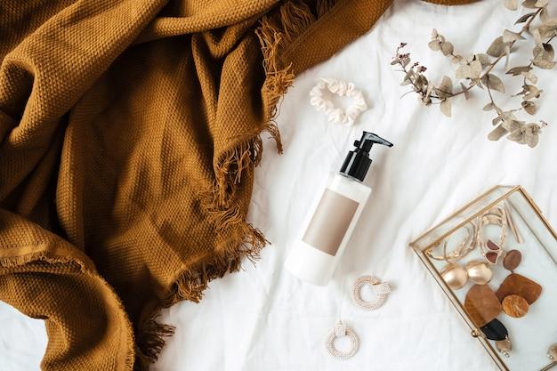 Bellezza, collage femminile di stile di vita di moda. bottiglia di crema, ramo di eucalipto, plaid allo zenzero, bigiotteria su lino bianco