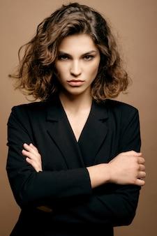 Modello di moda di bellezza con pelle pulita e capelli ricci in giacca nera sulla parete beige, donna seria di affari