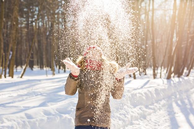 Ragazza di bellezza che soffia neve nel gelido inverno park. all'aperto. fiocchi di neve volanti.