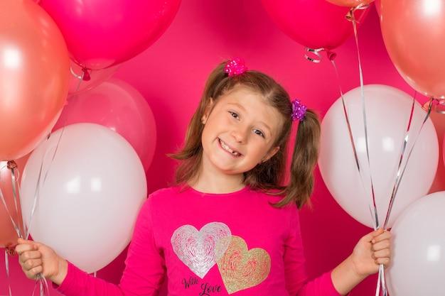 Ragazza di bellezza con mongolfiere colorate sorridente su sfondo rosa.