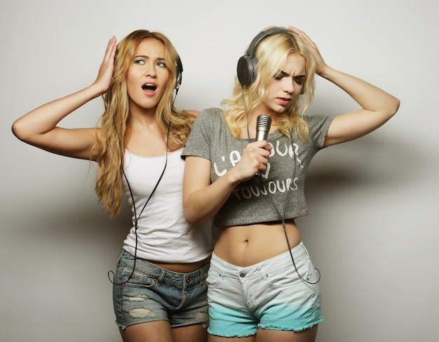 Ragazze di bellezza con un microfono cantando e ballando