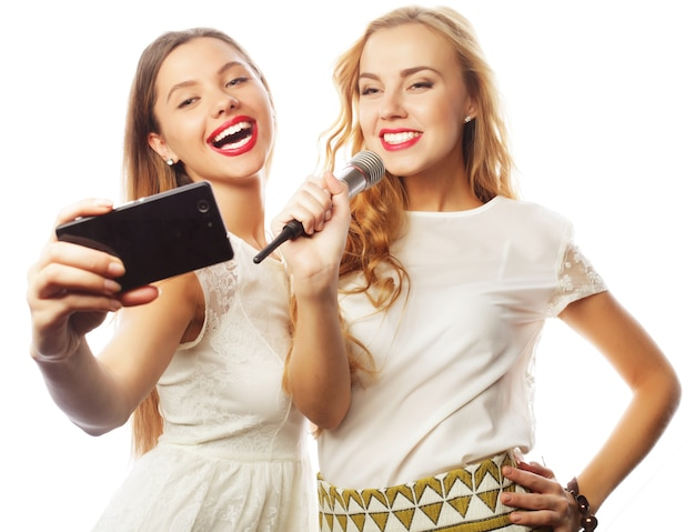 Ragazze di bellezza con un microfono che cantano e fanno selfie