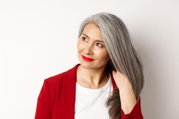 Concetto di bellezza e cura dei capelli. chiuda in su della donna senior asiatica elegante che mostra i capelli grigi lucidi e sani, sorridente e che osserva da parte, fondo bianco.