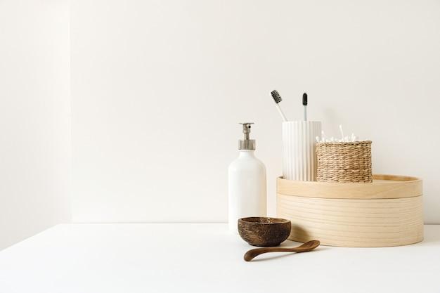 Composizione di assistenza sanitaria di bellezza con bastoncini per le orecchie in una bara di rattan, polvere, spazzolini da denti, sapone liquido sul tavolo bianco