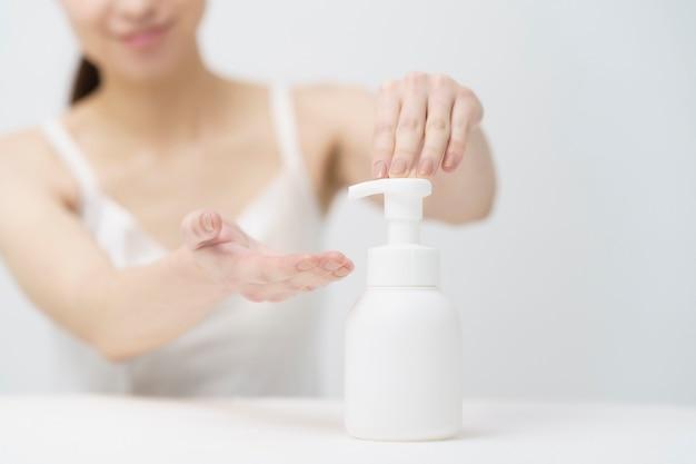 Immagine di bellezza e assistenza sanitaria / donna che fa schiuma da una bottiglia