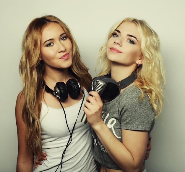 Ragazze di bellezza hipster con un microfono cantando e divertendosi