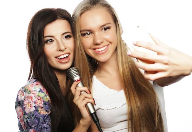 Ragazze hipster di bellezza con un microfono che cantano e fanno foto