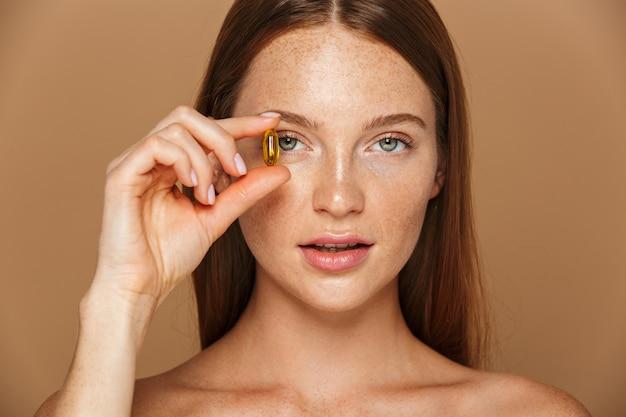 Immagine di bellezza della donna senza camicia caucasica 20s che tiene la pillola della vitamina, isolata sopra fondo beige