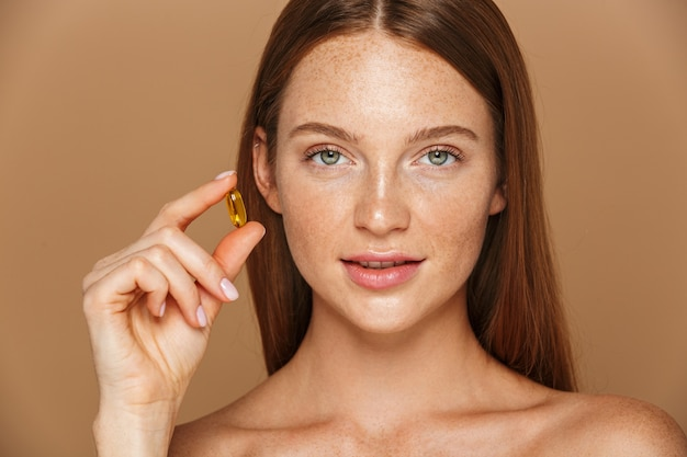 Immagine di bellezza della donna senza camicia europea 20s che tiene la pillola della vitamina, isolata sopra fondo beige