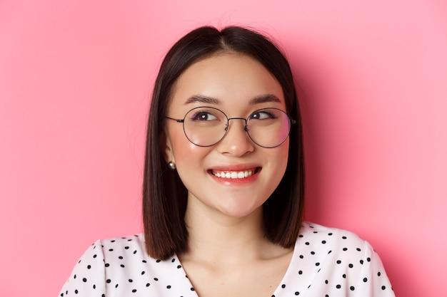 Concetto di bellezza e stile di vita. primo piano di una graziosa modella asiatica che indossa occhiali alla moda, sorride e guarda a sinistra lo spazio della copia, in piedi su sfondo rosa