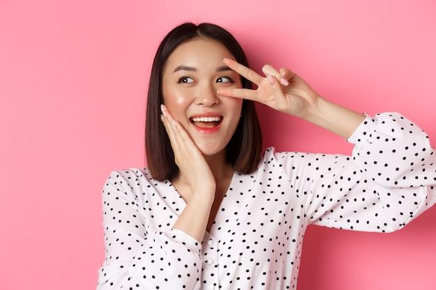 Concetto di bellezza e stile di vita. primo piano di una bella donna asiatica che mostra segno di pace e tocca la guancia, sorride felice alla telecamera, in piedi su sfondo rosa