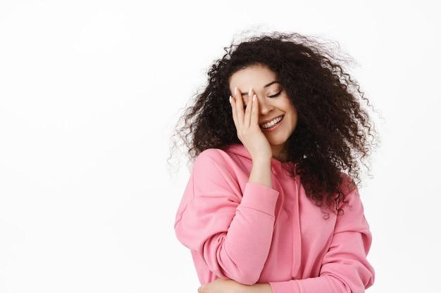 Bellezza e stile di vita. felice donna bruna con emozione sognante, che si tocca il viso e sorride civettuola, in piedi sul bianco