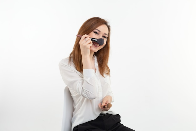 Artista di trucco di bellezza. close up coreano bella giovane donna abbastanza sorridente holding pennelli per il trucco sul muro bianco