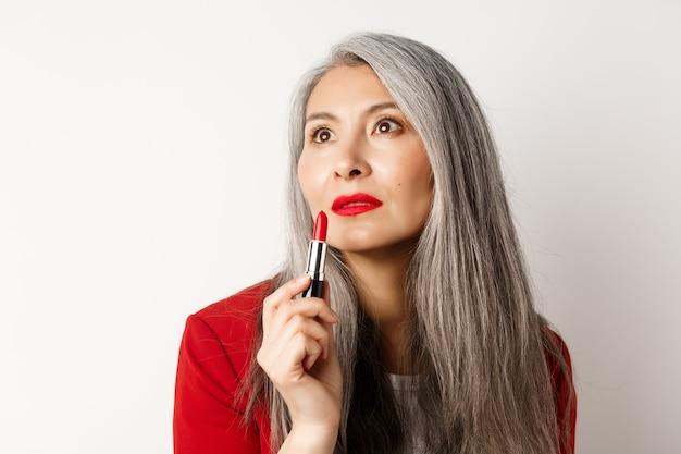 Concetto di bellezza e trucco. sensuale femmina asiatica matura con i capelli grigi, guardando da parte e mostrando rossetto rosso, in piedi su sfondo bianco.