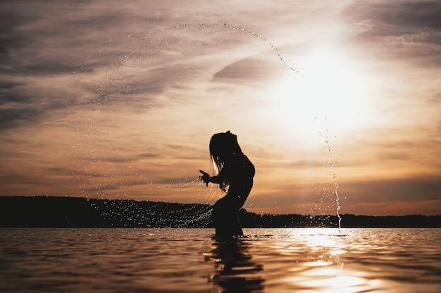 Ragazza di modello di bellezza che spruzza acqua con i suoi capelli