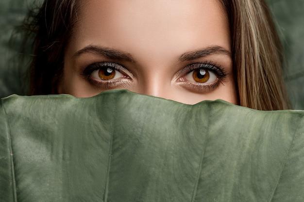 Modello di bellezza con perfetti occhi marroni e trucco naturale e foglie verdi.