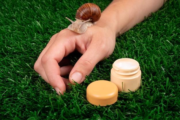 Bellezza, crema mani idratante con mucina di lumaca, cura della pelle, cosmetici per la cura del corpo su erba verde.