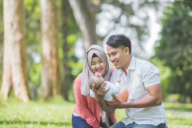 Madre e padre di bellezza con il loro neonato nel parco