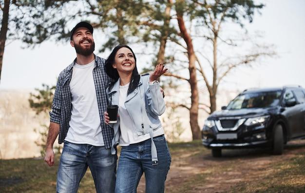 Bellezza della natura. la coppia è arrivata nella foresta con la loro nuova macchina nera