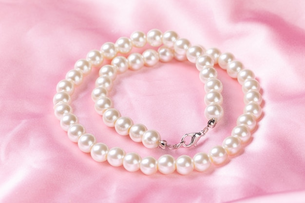 Collana di perle di bellezza su panno rosa