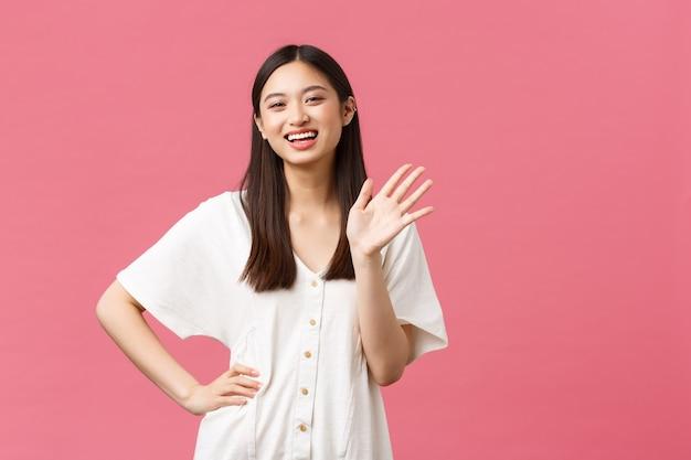 Bellezza, emozioni delle persone e concetto di svago estivo. amichevole ed estroversa ragazza abbastanza asiatica in abito bianco che saluta, agitando la mano e sorridendo allegro, salutando qualcuno ciao gesto.