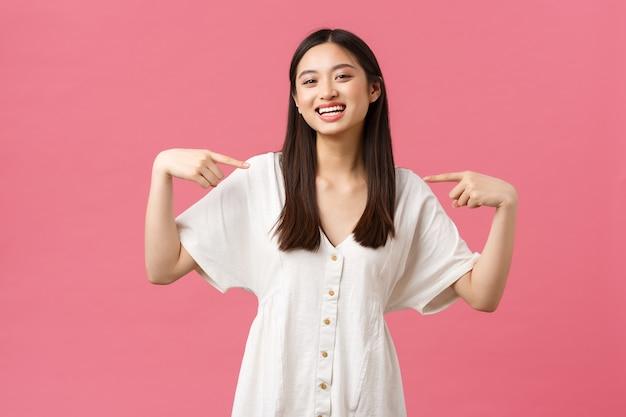 Bellezza, emozioni delle persone e tempo libero estivo e concetto di vacanza. entusiasta gioiosa ragazza asiatica carina in abito bianco, che indica se stessa con una faccia piacevole, volontaria, unendosi alla compagnia.