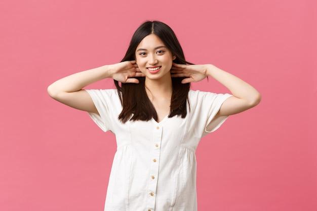 Bellezza, emozioni delle persone e tempo libero estivo e concetto di vacanza. donna asiatica sensuale e tenera che si vanta con taglio di capelli, capelli da esibizione dopo prodotti per la cura dei capelli o salone, sfondo rosa.