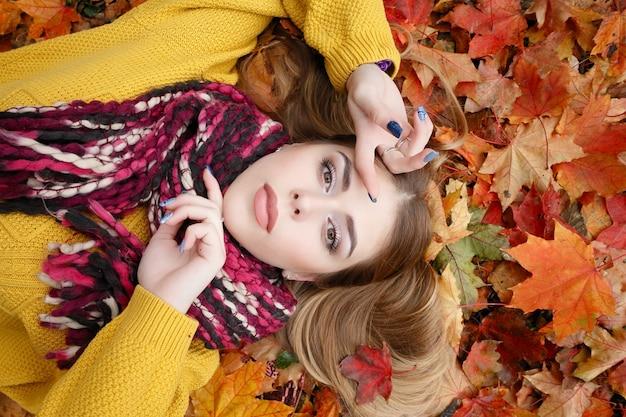 Concetto di bellezza, persone, stagione e salute - una bella ragazza giace in foglie autunnali rosse gialle