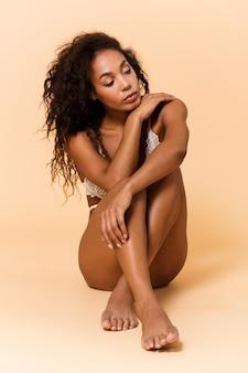 Ritratto di bellezza della donna afroamericana che indossa lingerie bianca, seduta sul pavimento isolato sopra il muro beige