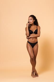 Ritratto di bellezza di incredibile donna che indossa lingerie nera, in piedi isolato sul muro beige