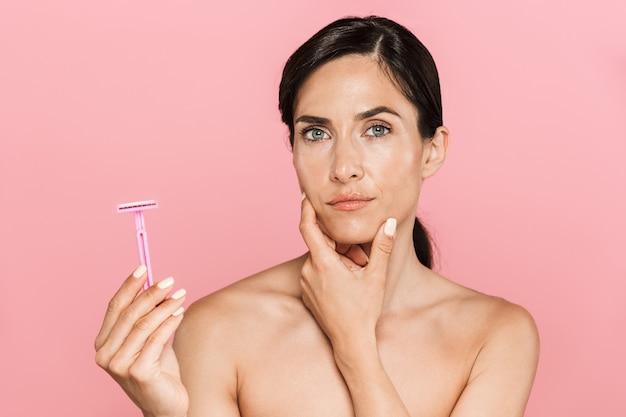 Ritratto di bellezza di un'attraente giovane donna in topless confusa in piedi isolata sul muro rosa, con in mano un rasoio
