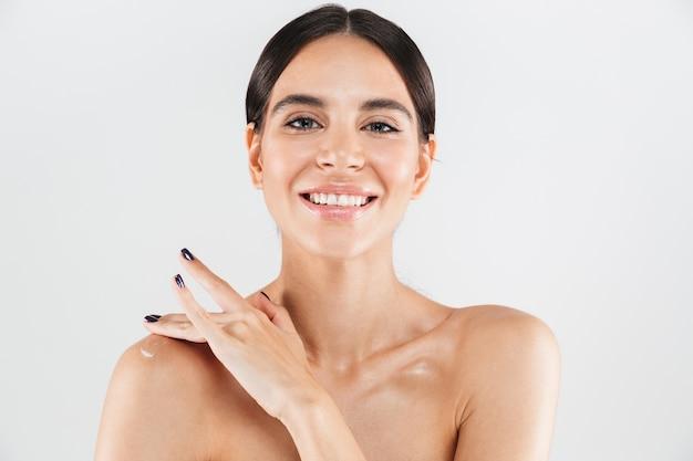 Ritratto di bellezza di una donna in buona salute attraente in piedi isolato sopra il muro bianco, applicando crema idratante sulla sua spalla