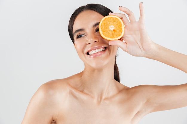 Ritratto di bellezza di una donna in buona salute attraente in piedi isolato sopra il muro bianco, in posa con la metà di un'arancia