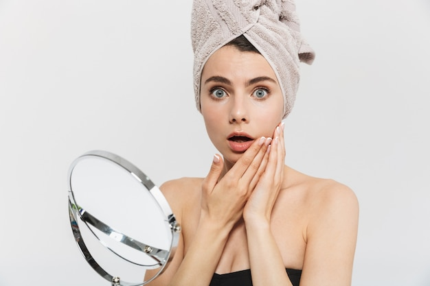 Ritratto di bellezza di un'attraente giovane donna sconvolta isolata su un muro bianco, guardando lo specchio, esaminando il viso