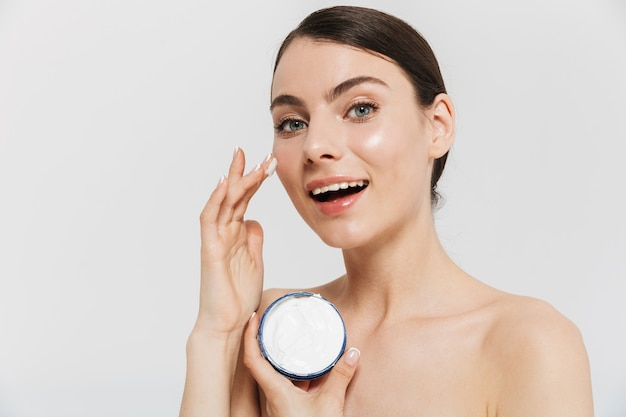 Ritratto di bellezza di una giovane donna bruna attraente in piedi isolata sul muro bianco, applicando la crema per il viso