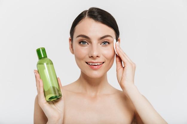 Ritratto di bellezza di un'attraente giovane donna bruna in piedi isolata su un muro bianco, mostrando una bottiglia con una lozione detergente