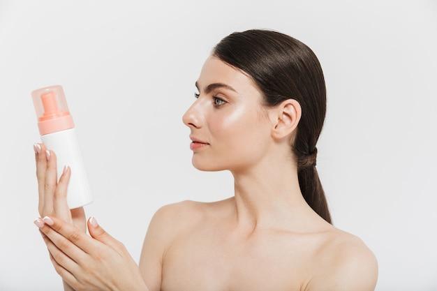 Ritratto di bellezza di un'attraente giovane donna bruna in piedi isolata su un muro bianco, mostrando una bottiglia con olio per il viso