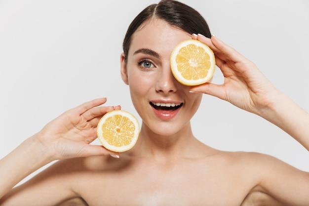 Ritratto di bellezza di una giovane donna attraente in topless isolata su un muro bianco, che mostra un limone a fette