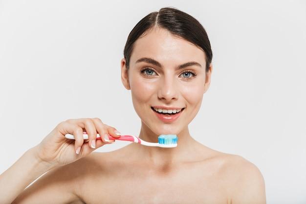 Ritratto di bellezza di una giovane donna attraente in topless isolata sul muro bianco, che mostra spazzolino da denti con dentifricio