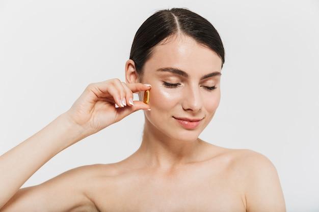 Ritratto di bellezza di una giovane donna attraente in topless isolata sul muro bianco, prendendo pillole di bellezza