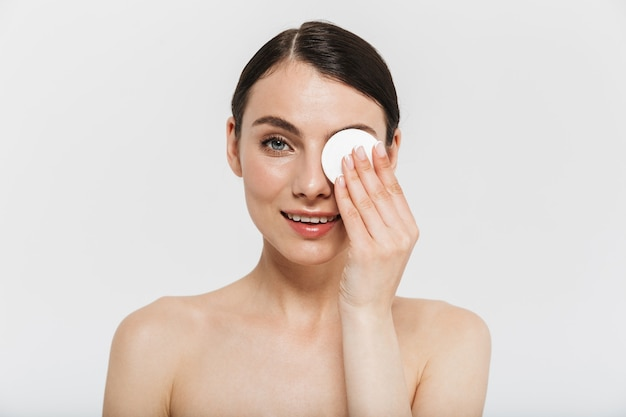 Ritratto di bellezza di una giovane donna attraente in topless isolata sul muro bianco, usando un batuffolo di cotone