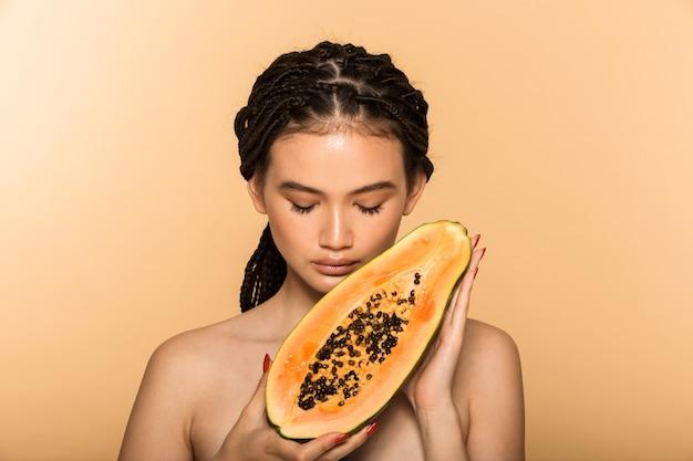Ritratto di bellezza di una giovane donna attraente in topless in piedi isolata sul muro beige, in posa con frutta di papaia