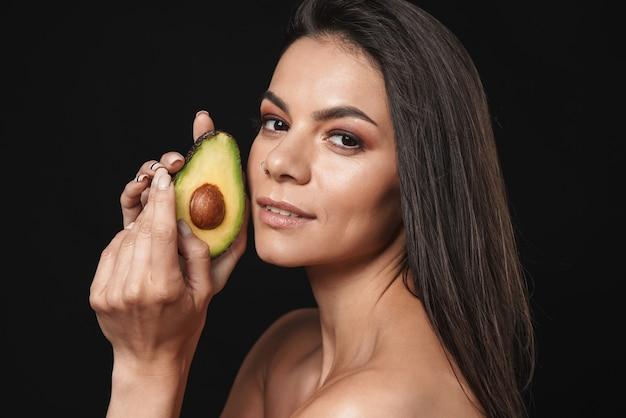 Ritratto di bellezza di una giovane donna attraente in topless con lunghi capelli castani isolati su un muro nero, in posa con avocado a fette