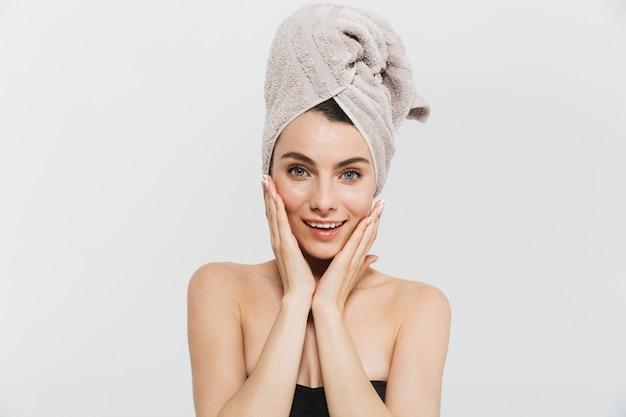 Ritratto di bellezza di una giovane donna attraente isolata sul muro bianco, con un asciugamano in testa