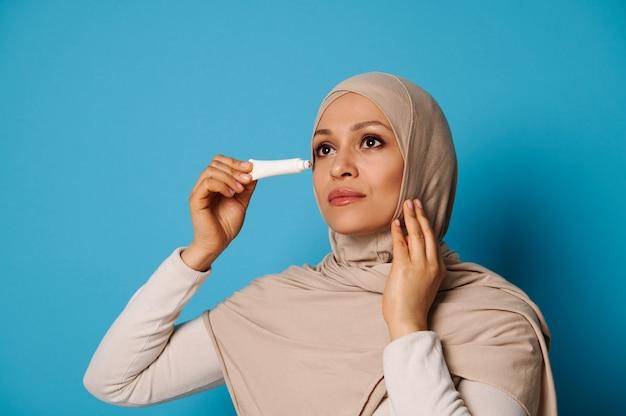 Ritratto di bellezza di bella donna araba con pelle perfetta che applica crema sotto gli occhi isolati
