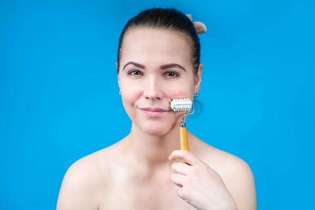 Ritratto di bellezza di bella ragazza felice, giovane donna che fa massaggio del viso con rullo di legno, massaggiatore