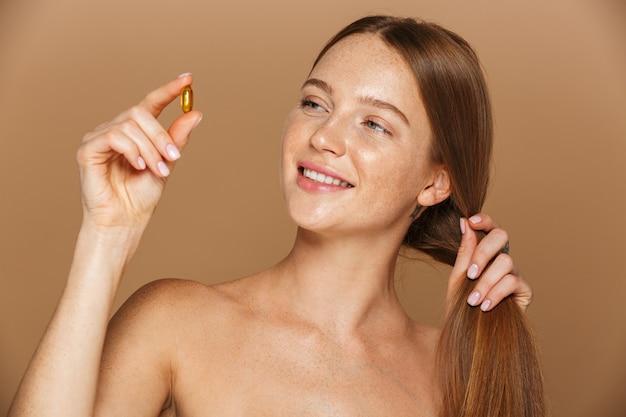 Ritratto di bellezza di una bella giovane donna in buona salute con lunghi capelli rossi che mostra la capsula vitaminica isolata sopra la parete beige