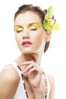 Ritratto di bellezza. bella ragazza alla moda con il fiore dell'orchidea nei capelli.