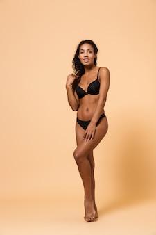 Ritratto di bellezza della donna castana che indossa lingerie nera, in piedi isolato sopra il muro beige